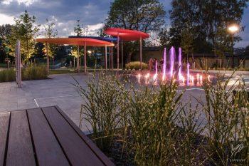 park sensoryczny, na zdjęciu wybetonowany plac, podświetlana fontanna oraz donice z roślinami