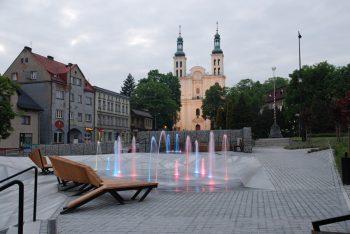 Rynek i bazylika w Pszowie foto. UM Pszów Na zdjęciu podświetlana fontanna oraz drewniane leżaki. W tle zabudowa miejska