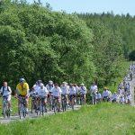Uczestnicy powiatowego rajdu rowerowego jadący peletonem; na zdjęciu kilkuset rowerzystów w białych koszulkach jadący malowniczą