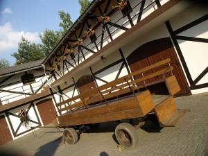 widok na stylizowaną stajnię - ujeżdżalnię koni, na pierwszym planie wóz drewniany