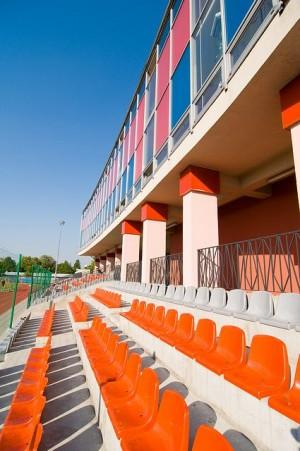 Powiatowy Młodzieżowy Ośrodek Sportu w Wodzisławiu Śl. na zdjęciu fragment stadionu lekkoatletycznego, budynek oraz krzesełka stadionowe