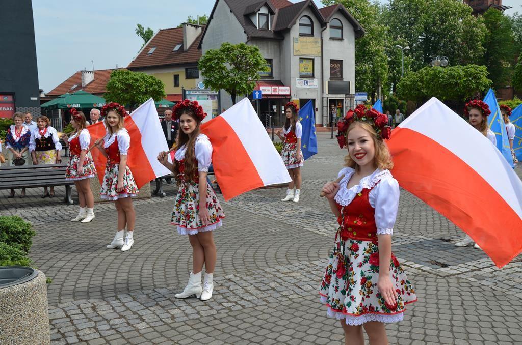 Zdjęcie przedstawiające młode kobiety w strojach ludowych powiewające polską flagą narodową