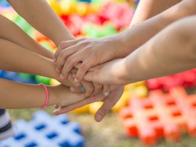 ręce kilku osób złożone w geście wzajemnego wsparcia