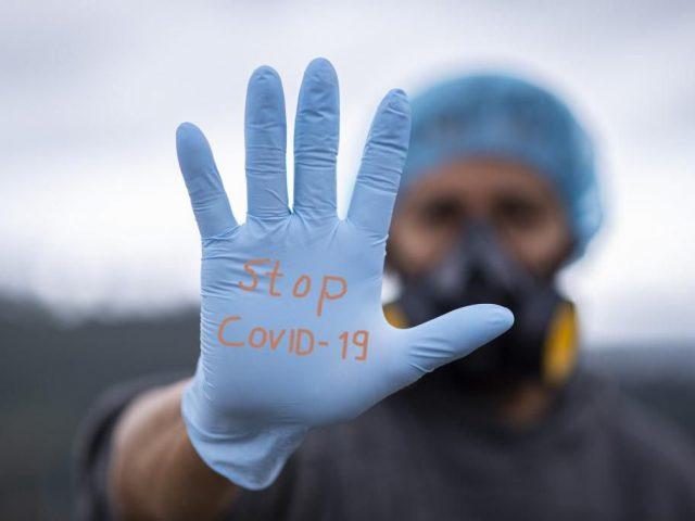uniesiona ludzka dłoń w ręwkawicy jednorazowej z napisem stop covid-19