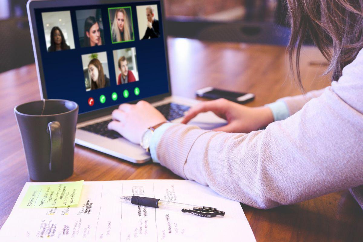 konferencja online, postać ludzka oparta pracująca n komputerzez, na monitorze widocznych parę postaci ludzkich