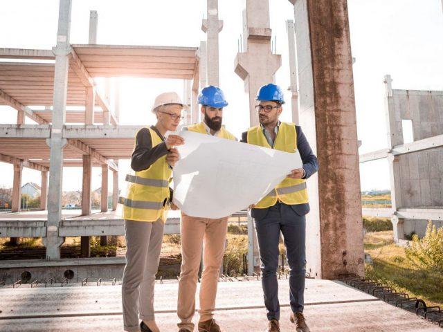 architekci omawiają projekt budowlany, w tle trwająca budowa obiektu