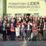 Zdjęcie zbiorowe laureatów tytułu Powiatowych Liderów Przedsiębiorczości 2019-2020 wraz z samorządowcami i przedstawicielami Cechu w Wodzisławiu Śląskim. Foto na schodach MOK Radlin