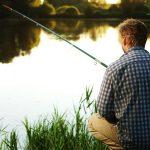 wędkarz łowiący ryby nad brzegiem zbiornika wodnego