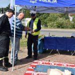 akcja Road Safety Days w Wodzisławiu Śl. 21 wrzesnia 2021 na zdjęciou kierowca przygotowujący się do ćwiczeń pierwszej pomocy w asyście policjanta i strażaka