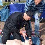 akcja Road Safety Days w Wodzisławiu Śl. 21 wrzesnia 2021, na zdjęciu strażak udziela instruktażu na fantomie jak unieść podbródek ofiary, w tle kierowca przygądający się instruktażowi