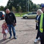 akcja Road Safety Days w Wodzisławiu Śl. 21 wrzesnia 2021, na zdjęciu kierowca z córką zainteresowani akcją w towarzystwie policnajta i pracownicy starostwa