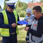 akcja Road Safety Days w Wodzisławiu Śl. 21 wrzesnia 2021, na zdjęciu kierowca trzymający na rękach dziecko, a policjant wręcza dziecku gadżet w postaci dmuchanej piłki