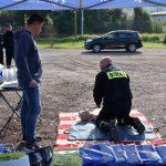 akcja Road Safety Days w Wodzisławiu Śl. 21 wrzesnia 2021, na zdjęciu kierowca oglądający instruktaż strażaka dotyczący udzielania pierwszej pomocy