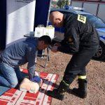 akcja Road Safety Days w Wodzisławiu Śl. 21 wrzesnia 2021, na zdjęciu kierowca pod okiem strażaka wykonuje rytmiczne uciski masażu serca na fantomie