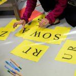 zdjęcie - uczestnicy warsztatów układają słowa z liter na paskach papieru