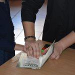 Ślubowanie pierwszaków w ZPSWR 2021 uczeń składa podpis pod przysięgą zbliżenie na odcisk palca
