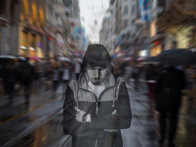 samotny mężczyzna otoczony tłumem, grafika przedstawiająca smutek i samotność
