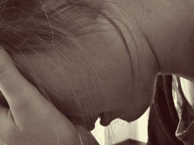 smutna kobieta zakrywająca twarz dłonią